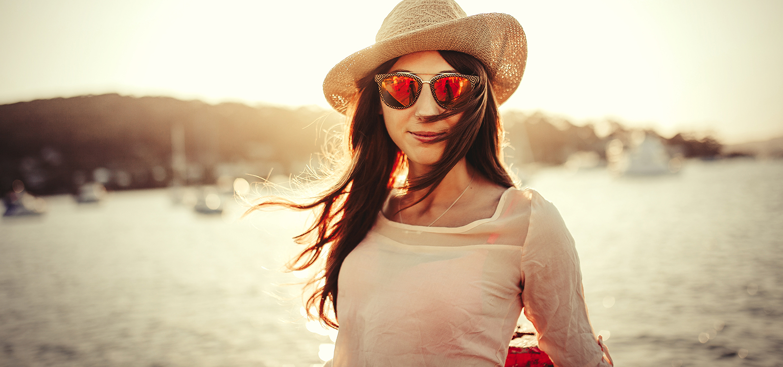 Woman with hat  and sunglasses posing at sunset with the sea in